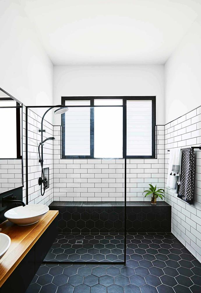 "In this [modern country farmhouse](https://www.homestolove.com.au/country-farmhouse-17468|target=""_blank"") a black and white palette was adopted for the bathrooms, paired with timber highlights. For the walk-in shower a black-framed glass screen is a striking feature and echoes the geometry of the hexagonal and subway tiles."