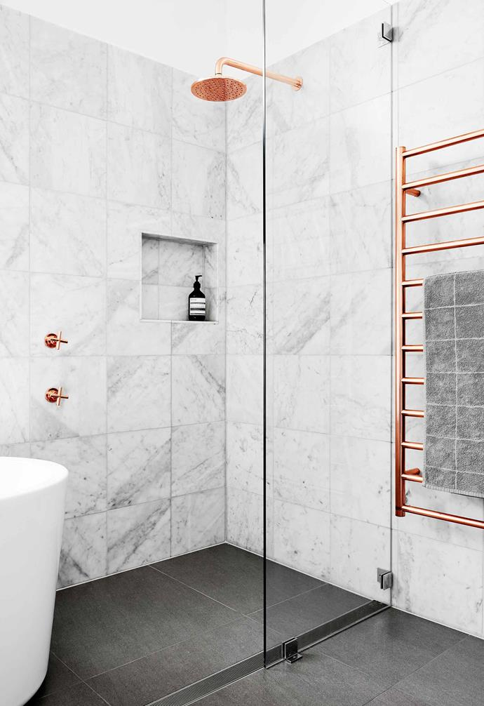 "Copper tapware and fixtures create a vibrant contrast in this [romantic meets industrial style bathroom](https://www.homestolove.com.au/a-luxe-copper-and-marble-bathroom-4680|target=""_blank""). Marble tiles on the walls and grey tiles for the floor create a warm neutral backdrop for the walk-in shower."
