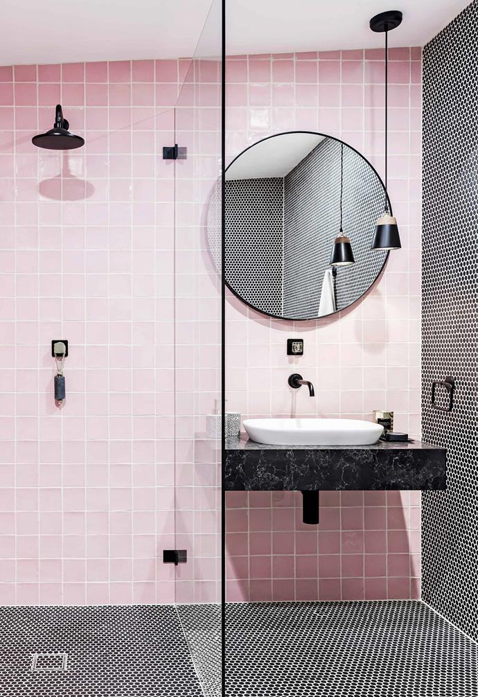 "In [Three Birds Renovations' revamp of a caravan and river shack](https://www.homestolove.com.au/three-birds-caravan-and-river-shack-renovation-5565|target=""_blank""), bright pink tiles were chosen for this playful bathroom space. Black pennyround tiles are paired with black fixtures and a black Caesarstone vanity add a striking contrast."
