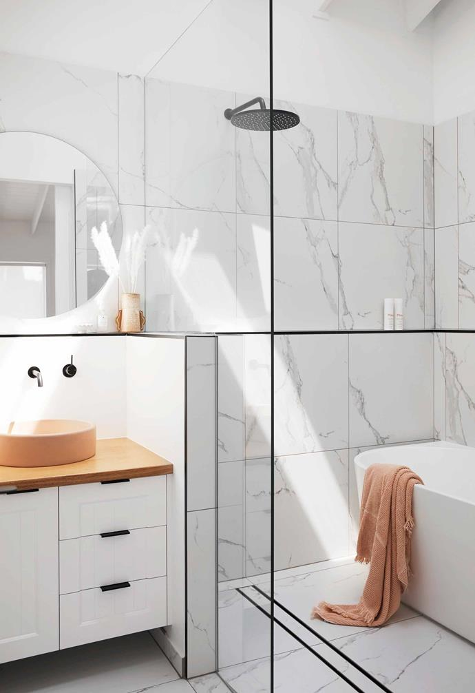 "Large-format marble tiles line the floors and walls of the relaxed bathroom in this [Gold Coast home](https://www.homestolove.com.au/ellie-bullen-gold-coast-home-20988|target=""_blank""). The walk-in shower zone has also managed to incorporate a freestsanding bathtub."