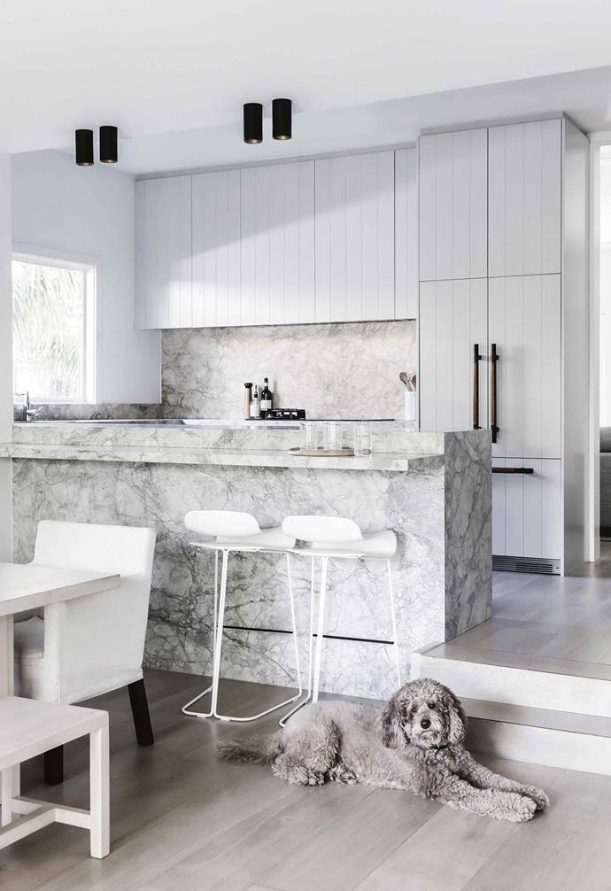 "All eyes are drawn to the lavishly veined Super White dolomite surface from CDK Stone on the splashback and benchtop in this elegant space. Given the close proximity of the dining space and the kitchen, the island in this renovated [weatherboard home](https://www.homestolove.com.au/bellamumma-nikki-yazxhi-home-tour-16880|target=""_blank"") is perhaps slimmer than most, but features a ledge that transforms the bench into a makeshift bar when the homeowners are entertaining."