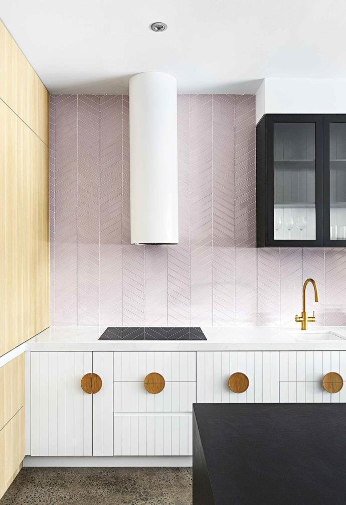 The interplay of shapes and lines in this stunning kitchen space conceived by GIA Bathrooms & Kitchens are highlighted thanks to round cabinet handles and the contrast of panelled cabinetry and the soft pink tiles laid in a chevron pattern.