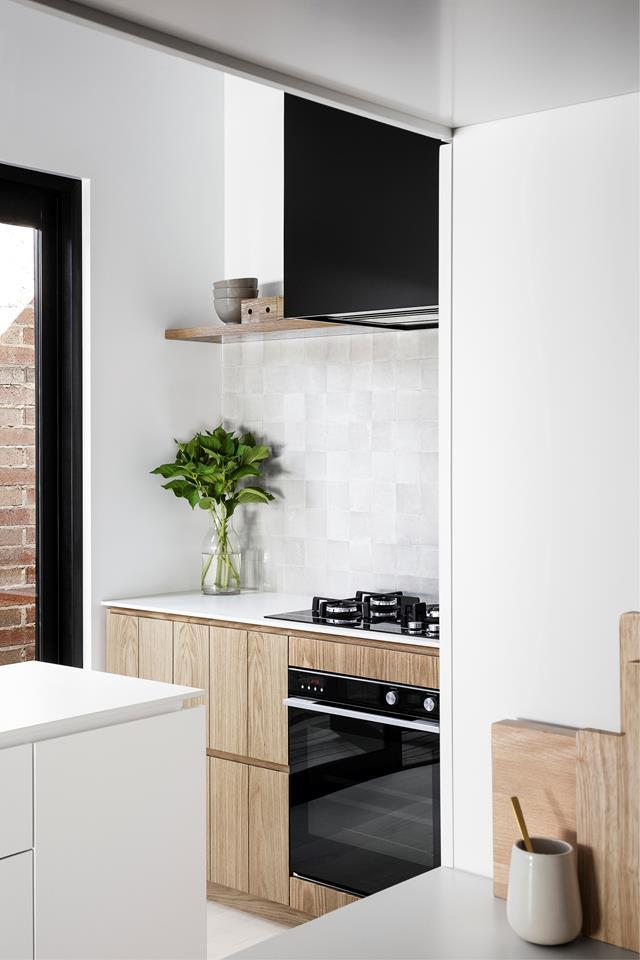 "This once dark and poky kitchen has been transformed with light and airy [Scandinavian style](https://www.homestolove.com.au/a-scandi-style-kitchen-makeover-6519|target=""_blank""). The narrow site largely dictated the layout of the kitchen: a long and narrow central island was needed to allow good traffic flow, while fully integrated whitegoods (fridge, freezer and dishwasher) were selected to minimise clutter."