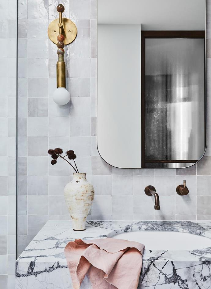 Mirrored cabinets: Custom made in Hazelnut Oak finish by Zuster from Reece. Basin Dado Australia 'Toronto' in Pearl White from Bathroom Collective. Basin tapware: Brodware 'Yokato' in Statue Bronze from Candana. Lighting: Apparatus Studio 'Talisman' sconces in agate, brass and leather from Criteria.
