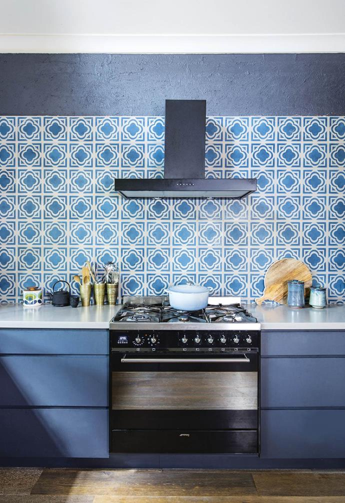 The Moroccan-style encaustic tiles on this splashback add a bohemian twist to this mostly dark-toned kitchen. The dramatic pattern is complemented by the soft grey benchtops and deep blue cabinetry.