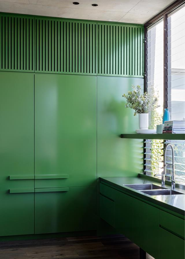 "The striking forest green kitchen in this [penthouse apartment](https://www.homestolove.com.au/a-rooftop-sydney-apartment-and-garden-5877|target=""_blank"") is slotted into the south-facing corner, while a cut-out diagonally opposite brings light and garden views inside. A green palette was used to link it with the outdoors."