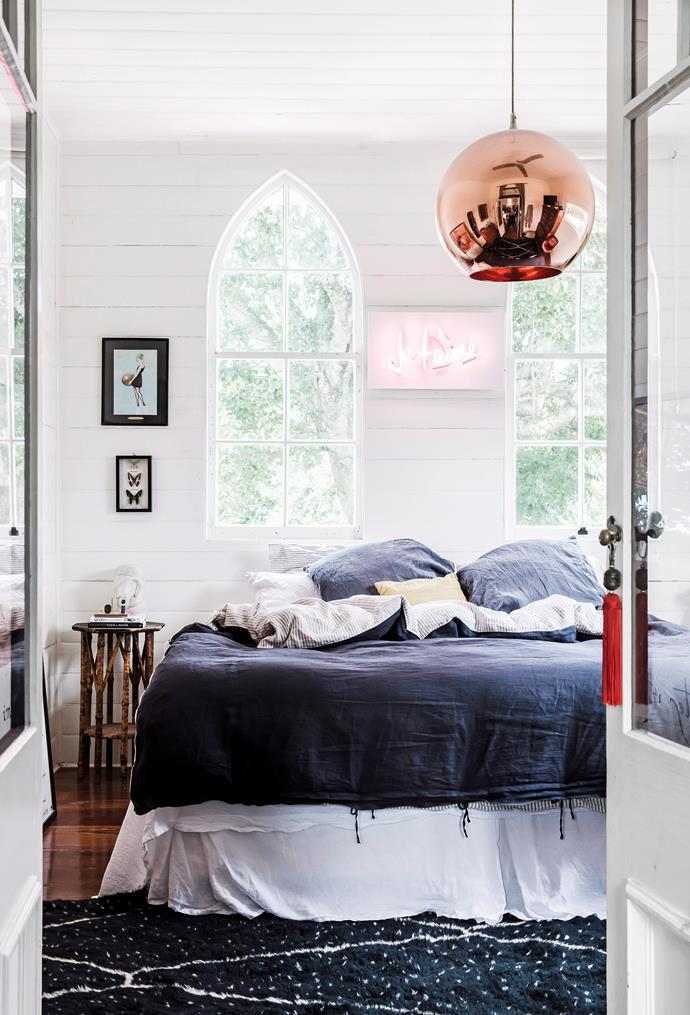 """This bedroom is heaven sent, quite literally! Part of a church conversion, this bedroom features the original church windows and high ceilings which are highlighted by the statement shiny pendant light. Layers of luscious bedlinen and a beautiful rug from [Tigmi Trading](https://tigmitrading.com/