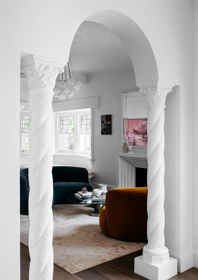 Moulded features are painted in Dulux 'Natural White'. Made by Storey 'Salon' engineered timber flooring and a custom Halcyon Lake rug add layers of tactility. Atop the Timothy Oulton 'Propeller' coffee table from Coco Republic and the fireplace are ceramics from Modern Times and Pépite. On the wall is a Heidi Yardley artwork from Nicholas Thompson Gallery; overhead hangs an Apparatus 'Cloud' pendant light from Criteria.