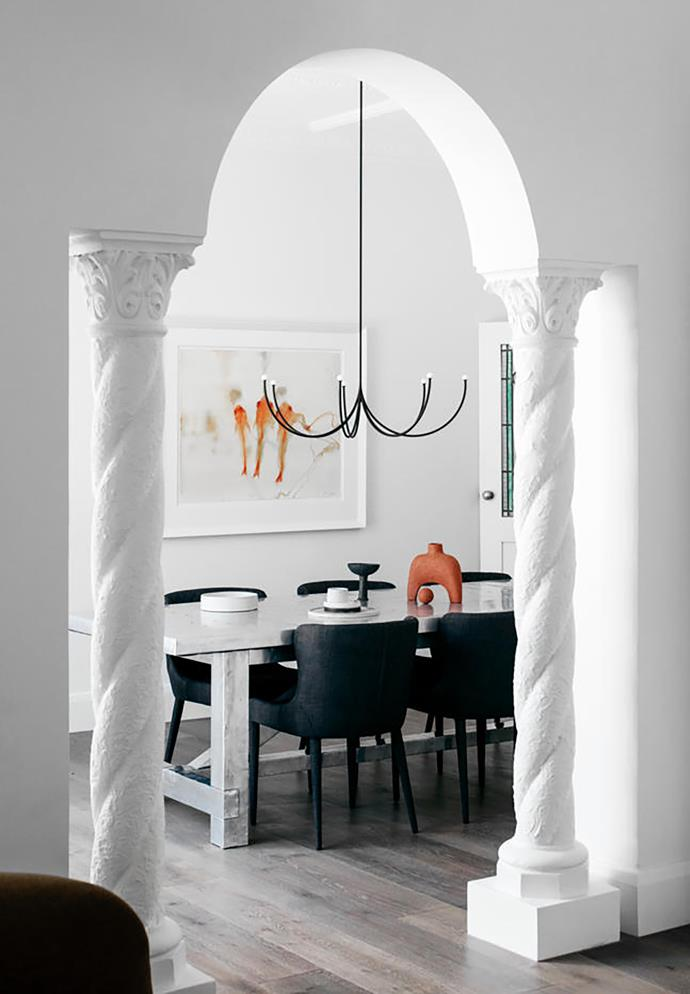 Archways and columns serve plenty of drama in the dining room, so Kathryn and Chris chose a spidery Matter Made 'Arca' pendant light from Criteria that wouldn't compete. The Timothy Oulton dining table and 'Saxon' chairs are from Coco Republic; the ceramics on top are from Modern Times and Pépite. The John Olsen artwork is from Metro Gallery.