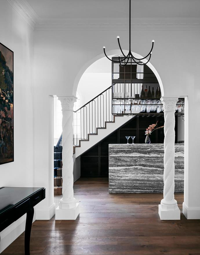 Bar made from Balthioul travertine from Signorino. The Vintec fridge under the stairs stores a curated selection of wines by Stocked Cellar. The vintage console is from Nicholas & Alistair and the artwork is by Adam Pyett from Sophie Gannon Gallery.
