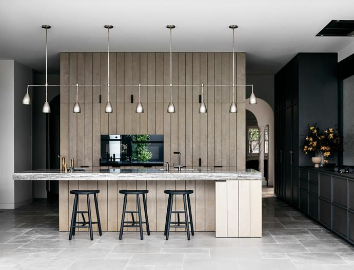 Pinstriped custom joinery handsomely conceals the butler's pantry. Above the Balthioul travertine island hangs an Apparatus 'Twig' pendant light custom made in a tarnished silver finish. Garonne limestone from Eco Outdoor was a wise choice for the flooring. Billiani 'Puccio' stools from Hub.