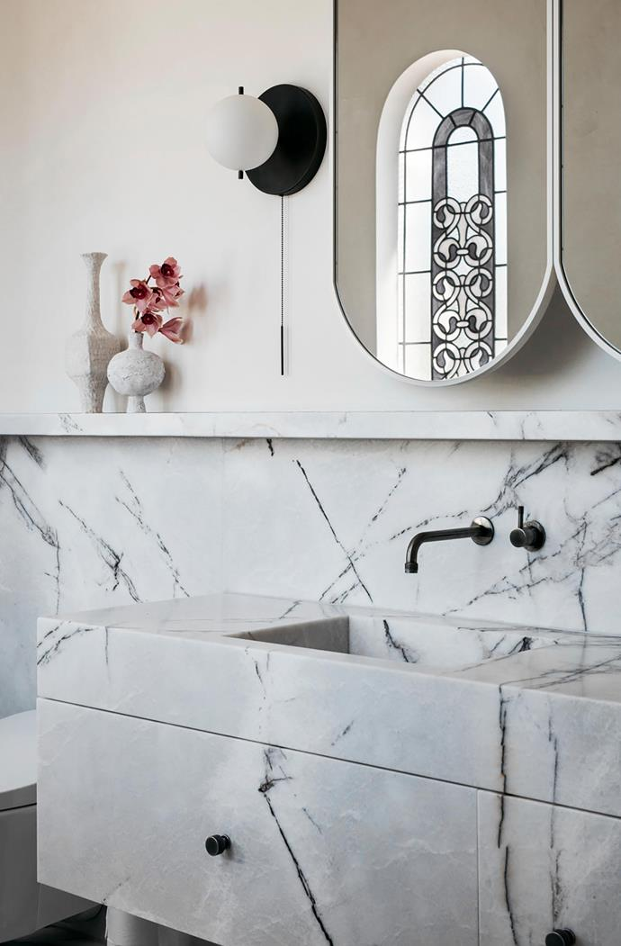 """""""The owners love marble but they didn't want tiles, so we went with slabs,"""" Chris says of the master ensuite. Inspired by the stained-glass windows, they opted for marble with tones of bluish purple from Signorino and designed the mirrors. Brodware 'Yokato' tapware and a Workstead 'Signal' sconce from Luke Furniture complete the scheme."""