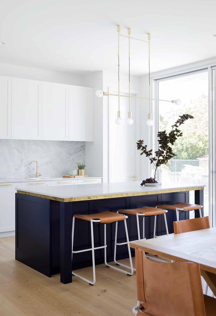 """A Volker Haug brass pendant light is the crowning feature in the generous kitchen of this [all-white Hamptons-style home in Sydney](https://www.homestolove.com.au/all-white-hamptons-style-home-21036