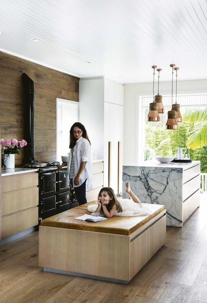"""Four copper pendant lights hang over the statement marble kitchen island in the kitchen of this [eco-friendly weatherboard house in Freshwater](https://www.homestolove.com.au/eco-friendly-weatherboard-house-freshwater-17440