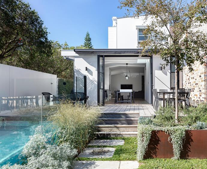 The garden, designed by Michael Cooke, is stepped down towards a studio space at the rear of the property. Cane-line 'Breeze' lounge chairs, Fast Spa 'Grande Arche' dining table and 'Easy' dining chairs, all from HG Furniture Solutions.