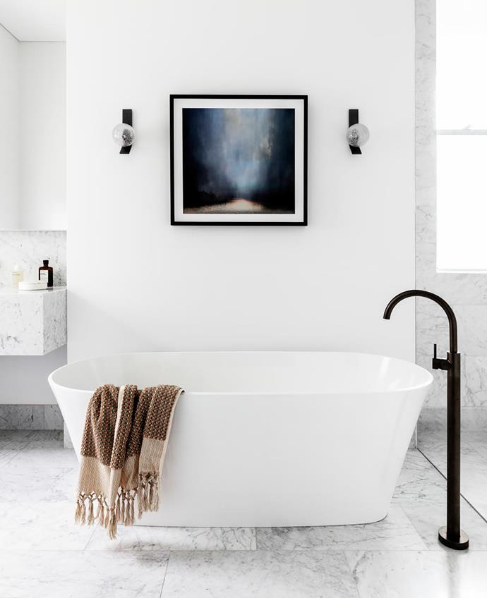 In the main ensuite, 'Duo' wall sconces from Articolo. 'Icon' tapware in Iron Bronze from Astra Walker. Vanity in Carrara marble from Mediterranean Marble. Victoria + Albert 'Vetralla' freestanding bath from Cass Brothers. Artwork by Sophia Szilagyi from Otomys Contemporary.