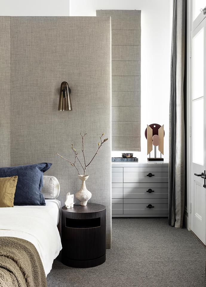 Looking past the custom bedhead in Kvadrat 'Clara 2' fabric and into the walk-in robe where a Giobagnara 'Tabou' sculpture from Becker Minty stands atop the drawers. 'Aatuti' bedside table by Hans Freymadl from Stylecraft with vessel by Alana Wilson and sculpture by Natalie Rosin.