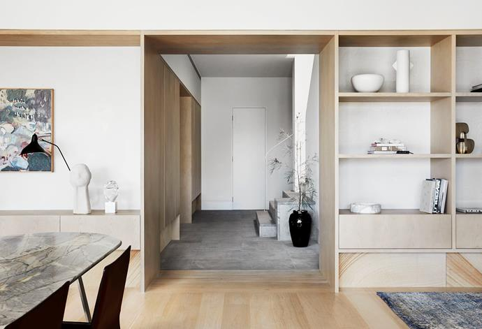 In the combined living and dining area, custom timber joinery is backed with polished plaster to suffuse the natural light, while the sandstone skirting reflects the natural landscape. Above the built-in sideboard is an artwork by Amy Wright titled You Yangs 1. The dining table was also custom made.