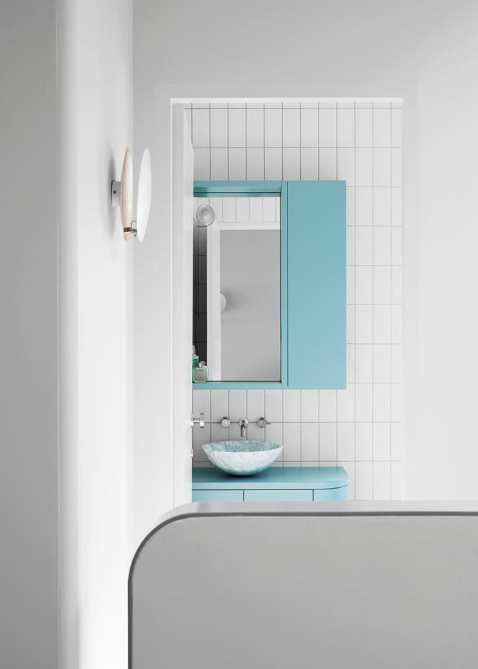 In this upstairs bathroom, Anna went for laminate-finished, curved custom joinery in a lighter shade of blue. She also chose Classic Ceramics 'Vogue' wall tiles in Latte and a Gallaria 'Abello' marble basin.