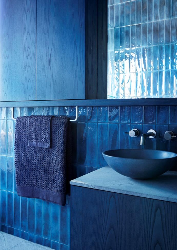 Multiple textures create visual interest and depth in this blue bathroom. Surface Gallery glazed wall tiles in Deep Ocean contrast with the grain of the blue-washed timber veneer joinery, the sandblasted marble floor tiles, and the towels from Hub. The benchtop is made from the same marble in a honed finish, the 'Sienna' basin is from Concrete Nation and the brushed platinum 'Icon' tapware is from Astra Walker.