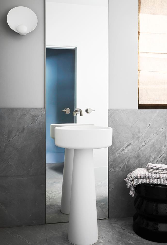 An Agape 'Bjhon' pedestal basin and custom mirror bring a sculptural element to the powder room. Pacific honed tiles from STS Stone and Astra Walker 'Icon' tapware complete the sophisticated scheme.