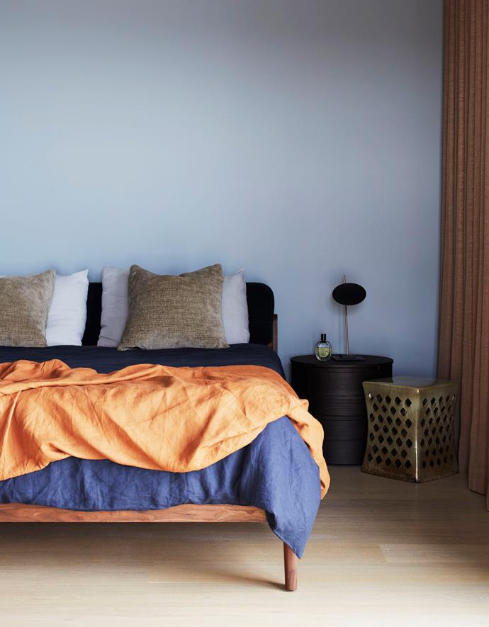 The master bedroom features a Neri&Hu 'Capo' bed, a 'Pinto' stool from MCM House and Fanuli bedside tables. Bedding by Cultiver and In Bed echo the room's rust-coloured Mokum linen curtains and walls painted in low-sheen Dulux 'Sepal'.