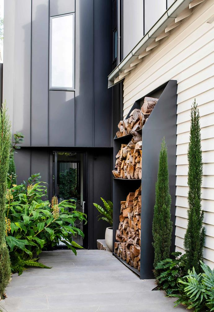 "In the [front garden](https://www.homestolove.com.au/front-garden-inspiration-17367|target=""_blank""), at the side entrance to the kitchen, a custom metal firewood cabinet stands guard with thriving plantings including yellow ginger lily (*Hedychium gardnerianum*) and Italian pencil pine (*Cupressus sempervirens* 'Glauca')."