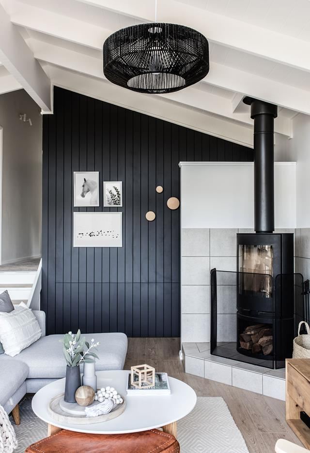 "Homeowners Karla and Andrew enlisted the help of interior stylist Catherine Heraghty of The Stables to renovate their [ski retreat](https://www.homestolove.com.au/explore-this-elegant-renovated-ski-retreat-in-jindabyne-7068|target=""_blank"") and transform it into something special. Black panelling complements the wood combustion fire place, creating the perfect nook to curl up in."