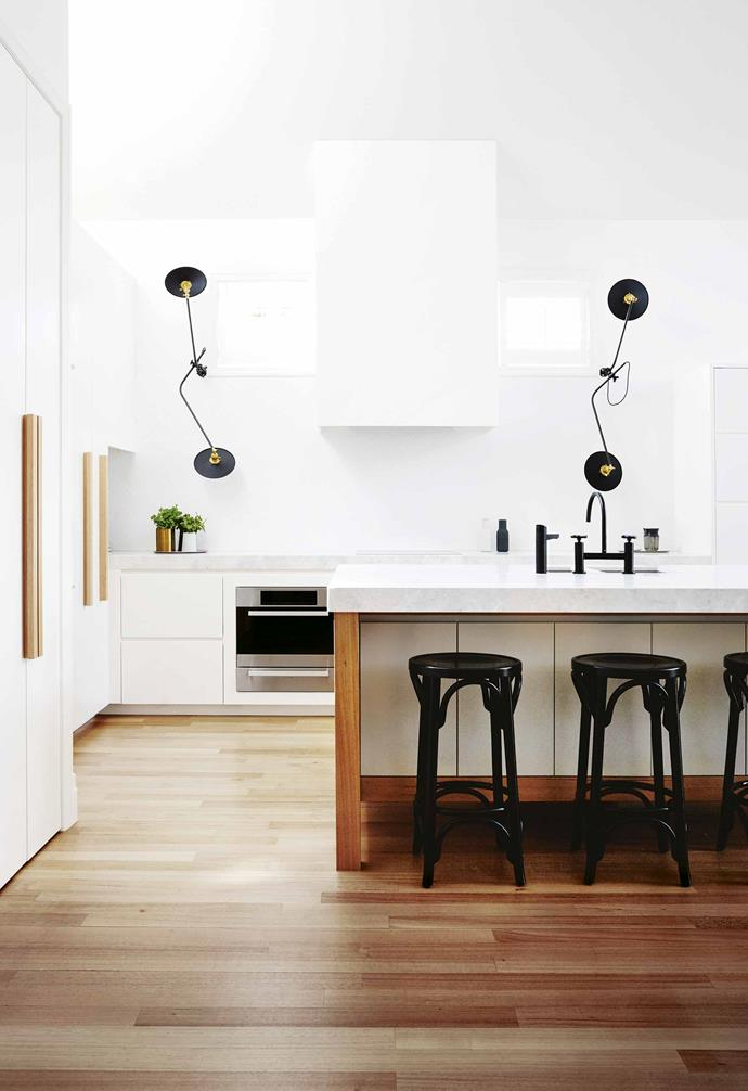 "**FEATURE LIGHTS**<br><br>The round black steel wall lamps are one of this kitchen's owner's favourite features. Sourced from Brooklyn-based design studio Workstead, they add a sculptural element that's often missing from kitchen design. They're also functional [task lighting](https://www.homestolove.com.au/task-lighting-ideas-20256|target=""_blank""), adding a hint of drama when the sun goes down. If you're sticking with neutrals — and aren't we all? — for your surfaces, consider a statement light to catch the eye and kick off the conversation.<br><br>"