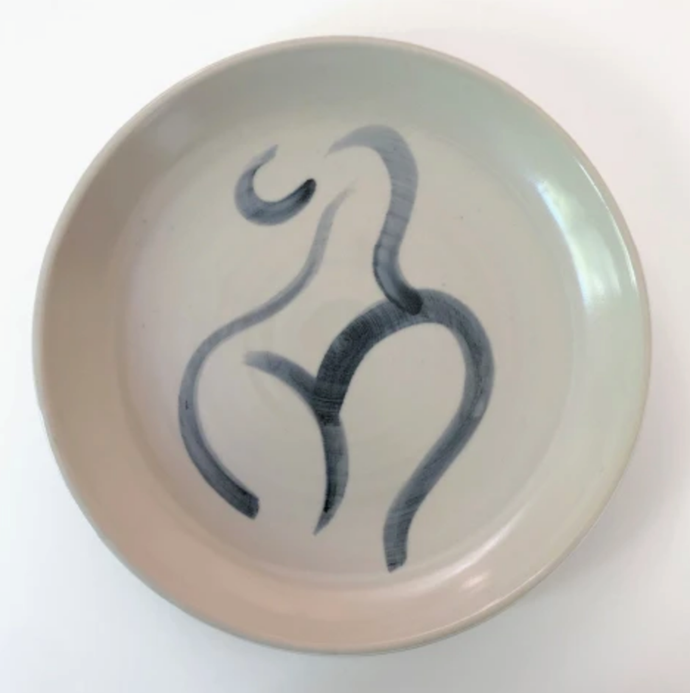 "The Curved Woman, stoneware plate, $320, by [Caroline Walls](https://www.carolinewalls.com/products/the-curved-women-03|target=""_blank"")."