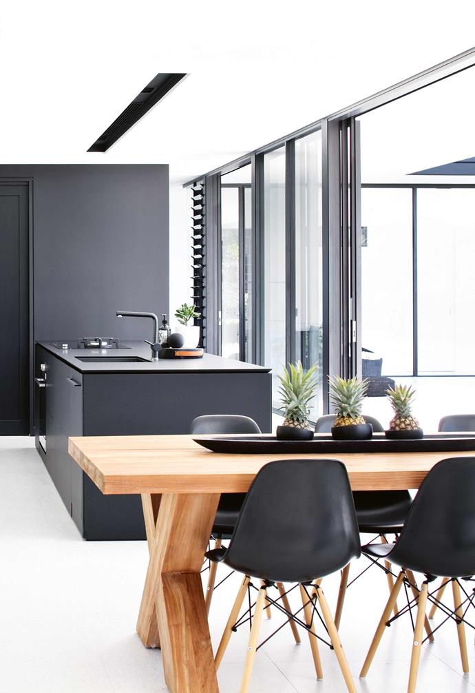 The couple built and sold two homes, but after discovering the perfect acreage in Noosa Waters, Queensland, just 10 minutes from the mainstrip, Sarah knew the time was right to realise the glass-box home she had wished for.<br><br>**Kitchen** This kitchen island features a black laminate benchtop from Fenix which pairs beautifully with the blach dining chairs.