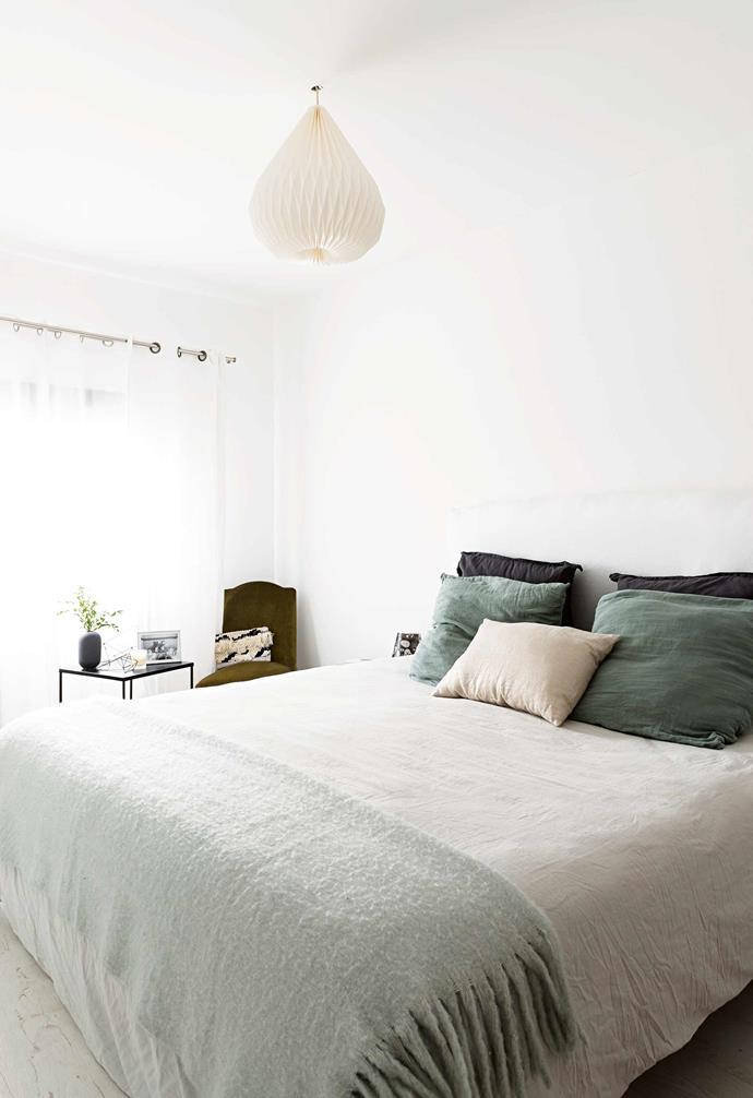 "The bedroom is an oasis of calm, with white walls, pale [timber flooring](https://www.homestolove.com.au/timber-floors-that-make-a-style-statement-2880|target=""_blank"") and a delicate lightshade. Comfort is key, with tactile layers in different shades of green softening the space and providing contrast. Sheer curtains are a perfect choice for a space where both natural light and privacy are important and a chair and table add extra relaxation space.<br><br>**TIP**: Hang [curtains](https://www.homestolove.com.au/how-to-choose-curtains-19711
