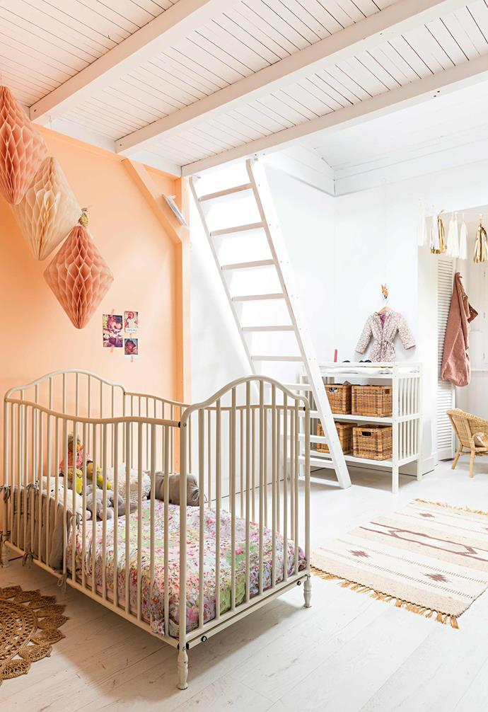 "Little Mila's bedroom is pretty in peach, with paper decorations matching the warm-toned wall. A collection of bird houses in varying sizes and colours hangs on one wall, with baskets and sacks [providing plenty of toy storage](https://www.homestolove.com.au/kids-storage-furniture-13865|target=""_blank"").<br><Br>**TIP**: Keep [kids' rooms](https://www.homestolove.com.au/modern-childrens-bedroom-ideas-13322