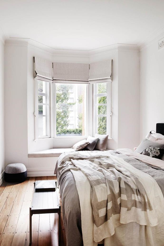 Painting the walls and ceiling in very slight variations of a single colour creates a seamless look in this bedroom. The pale timber flooring inspired the muted tones of the blinds, cushions and bedlinen, with darker accents creating depth.