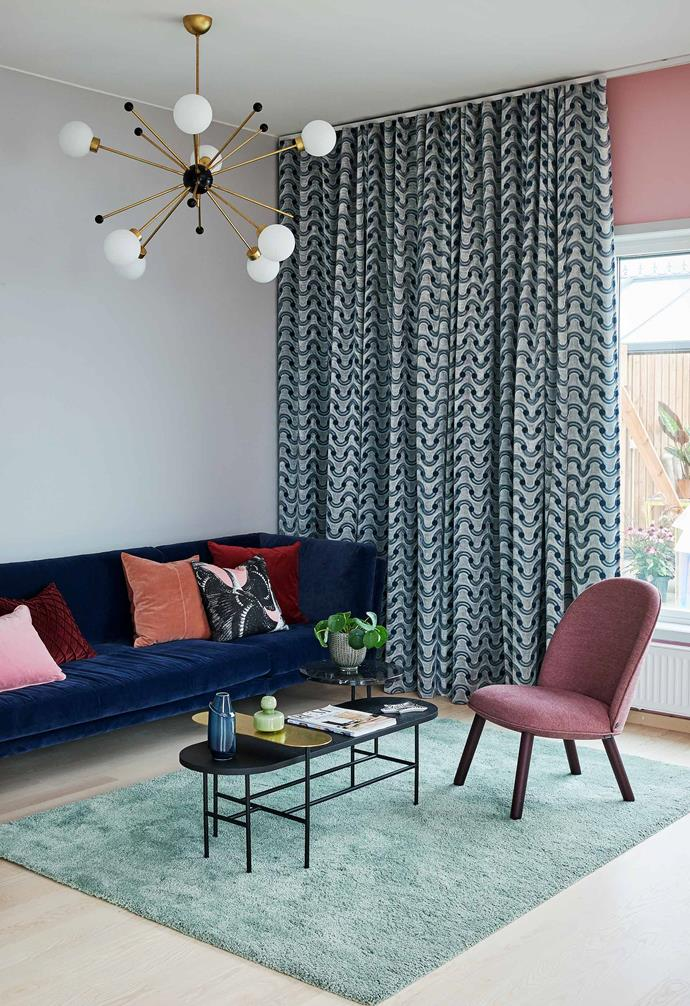 """**Living** A Bloomingville sofa in a dark blue velvet ties in with curtains by The Romo Group & Kirkby Design. Side table by [&Tradition](https://www.andtradition.com/ Target=""""_blank"""" rel=""""nofollow"""") used as a coffee table. Svenska Armaturer ball pendant lights."""
