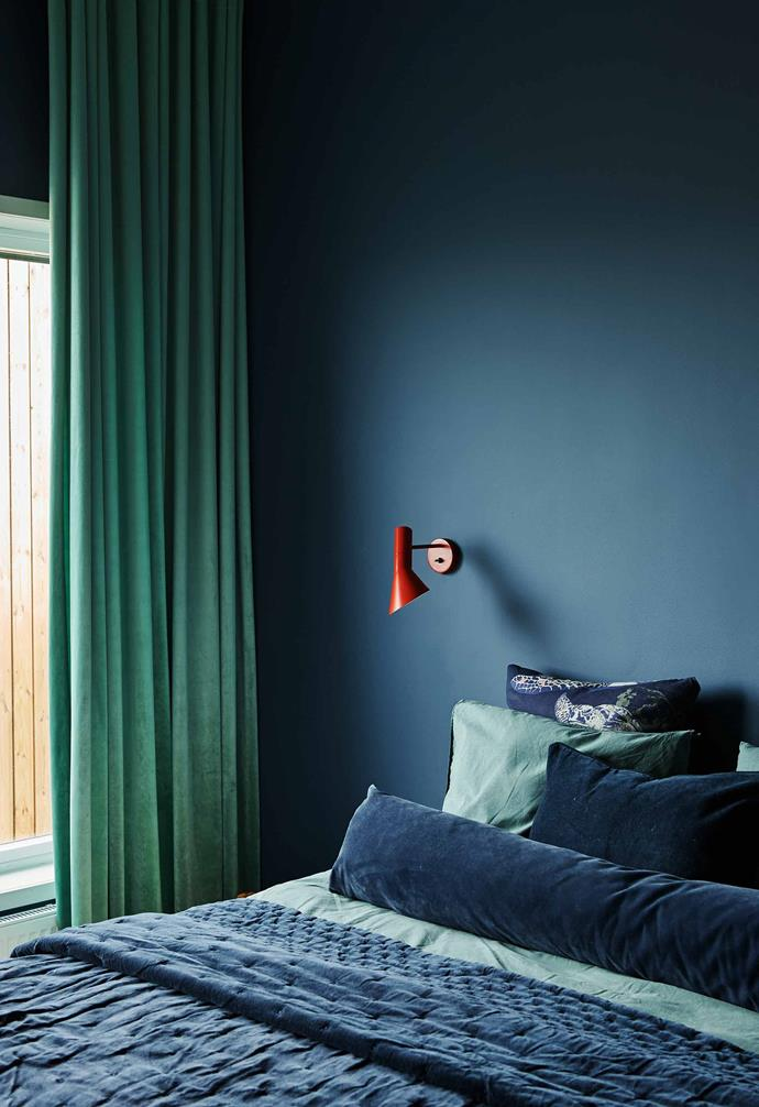 """**Bedroom** For the walls, Sara chose a restful, inky hue called Stiffkey Blue by  [Farrow & Ball](https://www.farrow-ball.com/ Target=""""_blank"""" rel=""""nofollow""""). Linen by Himla. Patterned pillows by fabric maker Studio Lisa Bengtsson. Louis Poulsen 'AJ' wall lamp."""