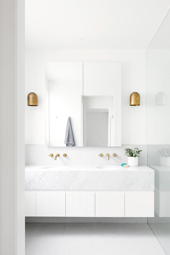 "A twin pair of brass wall lights from Anaesthetic Design pop against the all-white palette of the bathroom in this [contemporary home in Geelong](https://www.homestolove.com.au/contemporary-house-geelong-17561|target=""_blank""). The brass accents are complemented by brushed brass tapware."