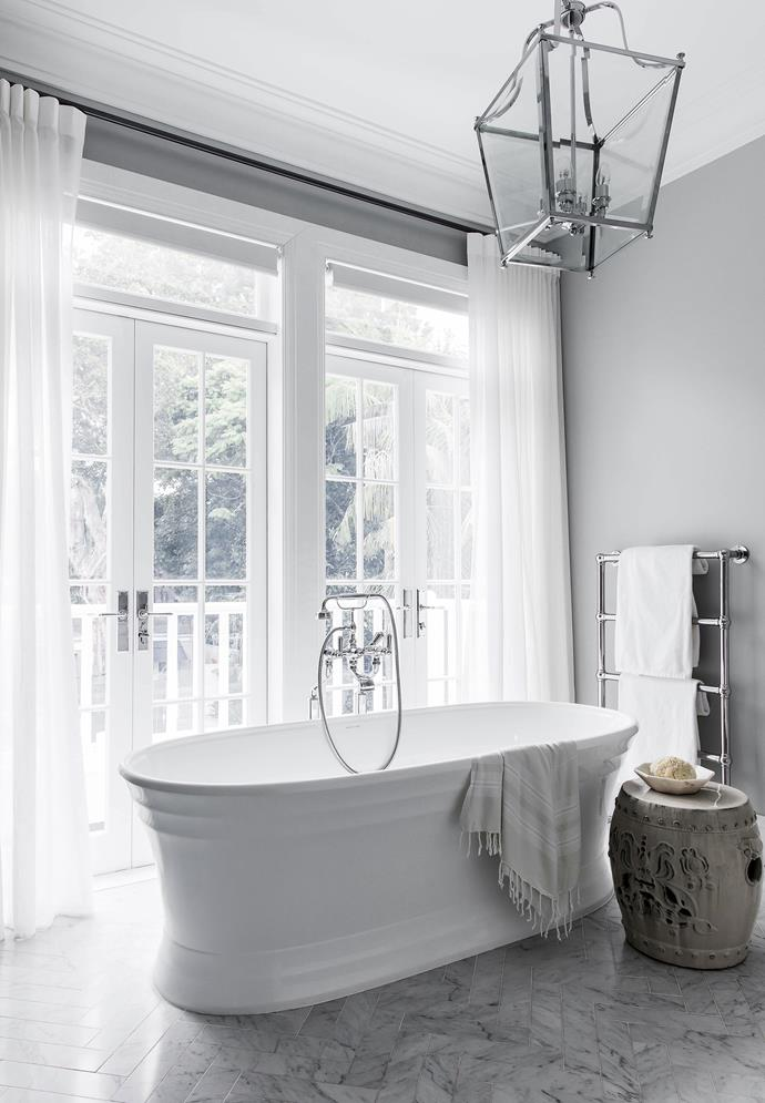 "Inspired by [Hamptons-style, this Sydney home](https://www.homestolove.com.au/a-luxurious-hamptons-style-home-in-sydneys-eastern-suburbs-6074|target=""_blank"") boasts a sophisticated all-white palette with elegant design choices. In the bathroom the freestanding bath tub sits under a glass pendant light that illuminates the whole room."