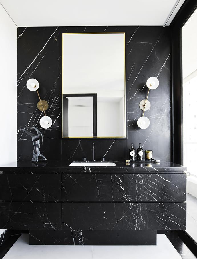 "Twin sculptural wall sconces from Apparatus Studio create a striking feature when paired with this dramatic black marble custom vanity in the bathroom of this [luxe Sydney apartment](https://www.homestolove.com.au/a-luxe-sydney-apartment-with-bespoke-interiors-19676|target=""_blank"")."