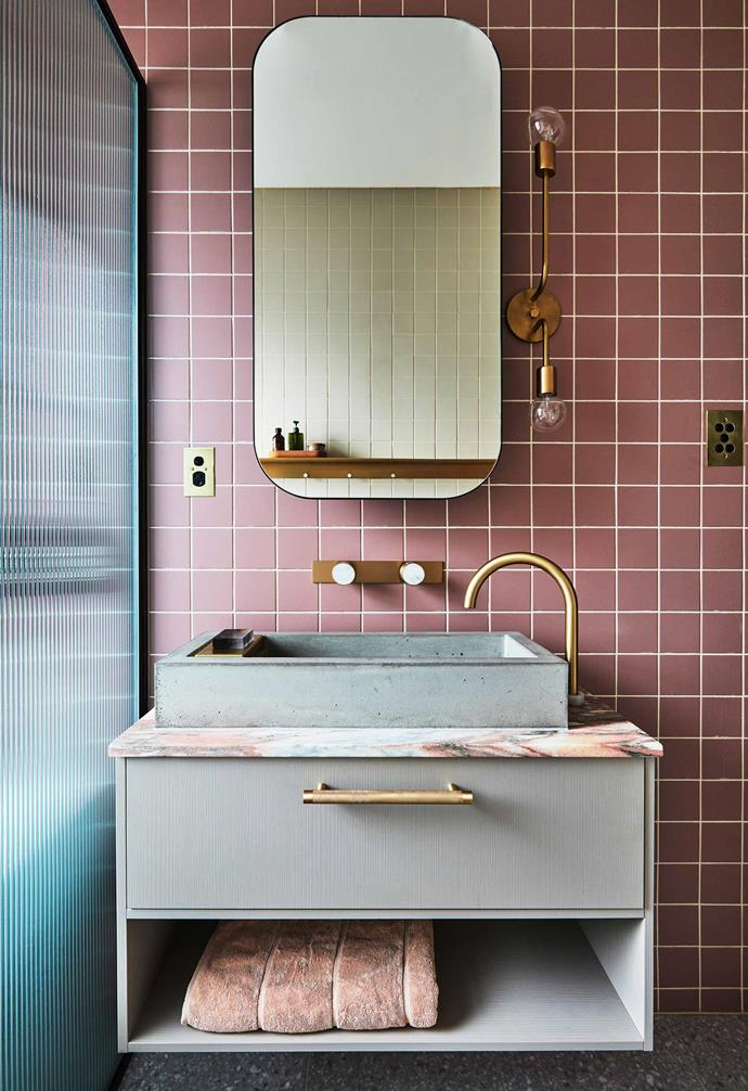 In the renovation of her compact Sydney apartment, interior designer Sophie Bowers added a slim-line wall light with twin globes to the side of her vanity. The brass fixture adds a touch of glamour that is complemented by the brass tapware and drawer pull.