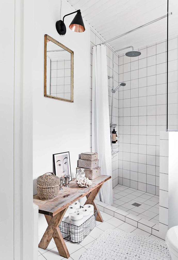 The home's details, including white-painted timber lining boards in the bedroom and kitchen, are a reminder of its original simplicity, with a stainless-steel and timber kitchen and white-tiled bathroom bringing the space up to date. Textures are kept natural and neutral, with several pieces of weathered timber and wicker furniture adding to the relaxed feel.<br><Br>**Bathroom** This practical zone also houses a washing machine. An old bench provides a spot for accessories, as well as wet-room essentials.