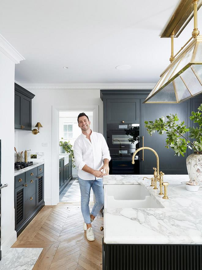 Steve Cordony in his kitchen at Rosedale Farm in Orange, NSW. Acquello fireclay sink in White and Perrin & Rowe 'Ionian' two-hole bench-mounted mixer with spray rinse in Polished Brass, all from The English Tapware Company.
