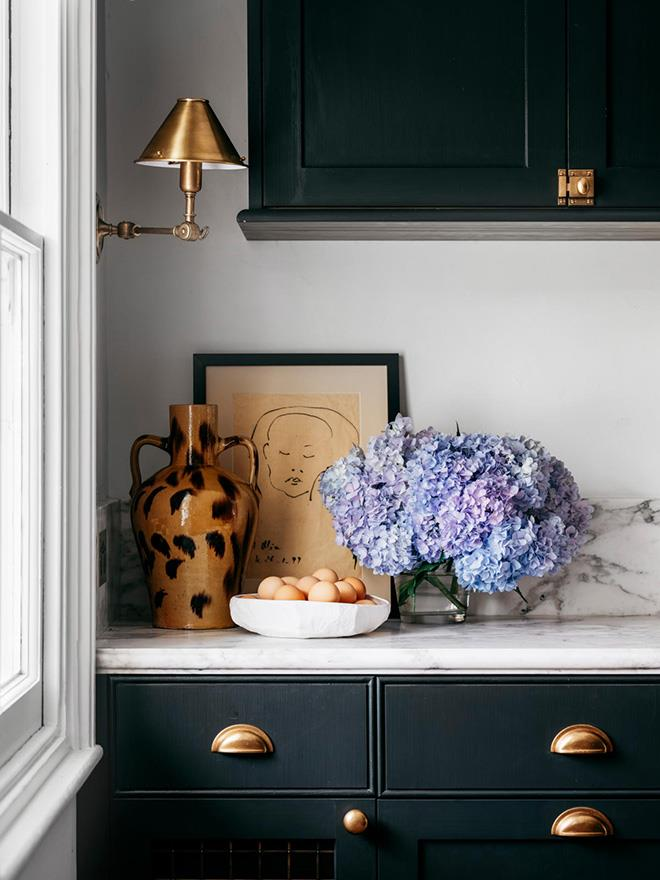 Exquisite details include the Ralph Lauren Home 'Anette' single sconce from The Montauk Lighting Co. and a vase from Tamsin Johnson. Custom cabinetry by Winchester Interiors with fold-back Häfele pocket doors in Porter's Paints 'Black Cockatoo'.