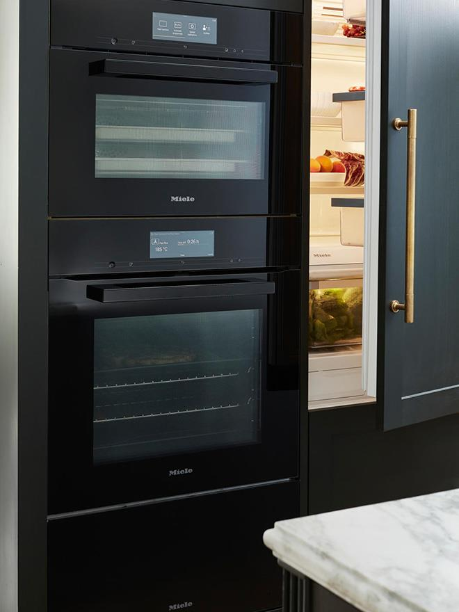 The Miele 'Generation 7000' oven, steam oven and warming drawer in Obsidian Black alongside the Miele 'Mastercool' integrated fridge and freezer.