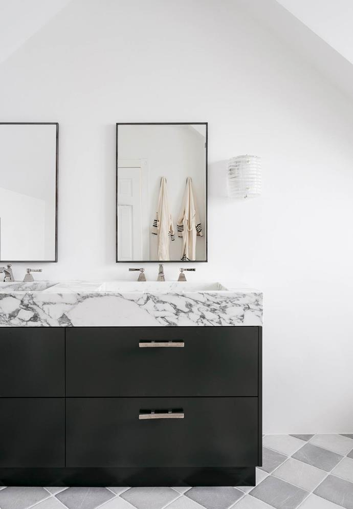 "Patterned grey tiles and a statement marble benchtop are paired with a black drawers and crisp white walls in the bathroom of this [classic Sydney home](https://www.homestolove.com.au/a-classic-sydney-home-decorated-with-contemporary-and-antique-pieces-20209|target=""_blank"")."