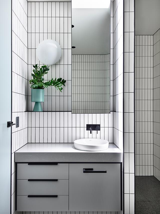 "A [triangular block became a functional family home](https://www.homestolove.com.au/triangular-block-home-design-19314|target=""_blank"") complete with this black and white bathroom that focuses on practicality. White subway tiles were laid vertically to accentuate height, with black grout creating a dynamic contrast."
