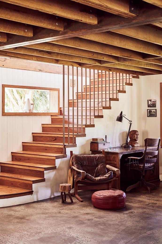 The stair banisters are made from recycled copper piping. The old leather chair — a mid-century Danish design that was bought second-hand — is one of David's prized pieces. Next to it is a drink stand made by Hannah, fashioned out of timber off-cuts.