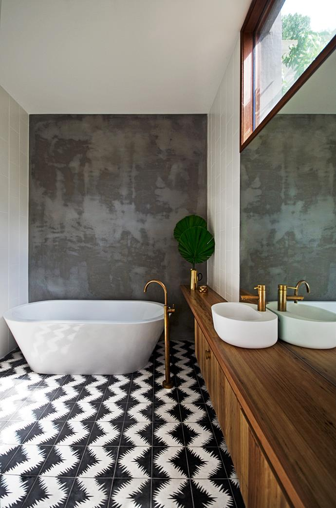 "A distressed concrete wall creates an industrial-style backdrop in the bathroom of [this striking bathroom](https://www.homestolove.com.au/bathroom-profile-brassed-beauty-2130|target=""_blank"") where patterned black and white floor tiles make a bold statement."