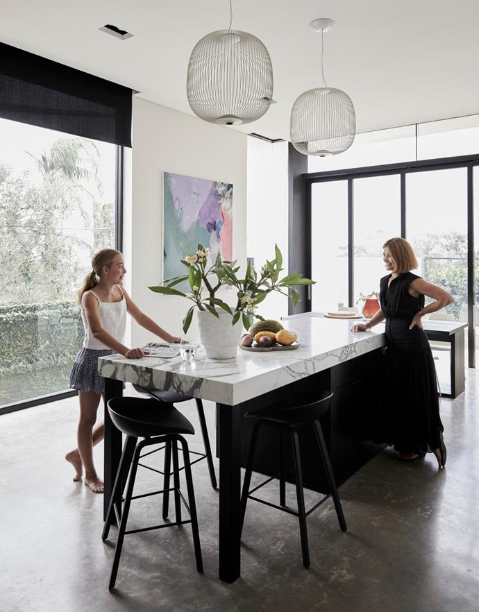 Kellie and Amelia at the marble kitchen island. Argo dining table by Antonia Citterio for Maxalto. Maui dining chairs by Vico Magistretti for Kartell, Space. About a Stool bar stools, Hay. Artwork by Miranda Skocsek.
