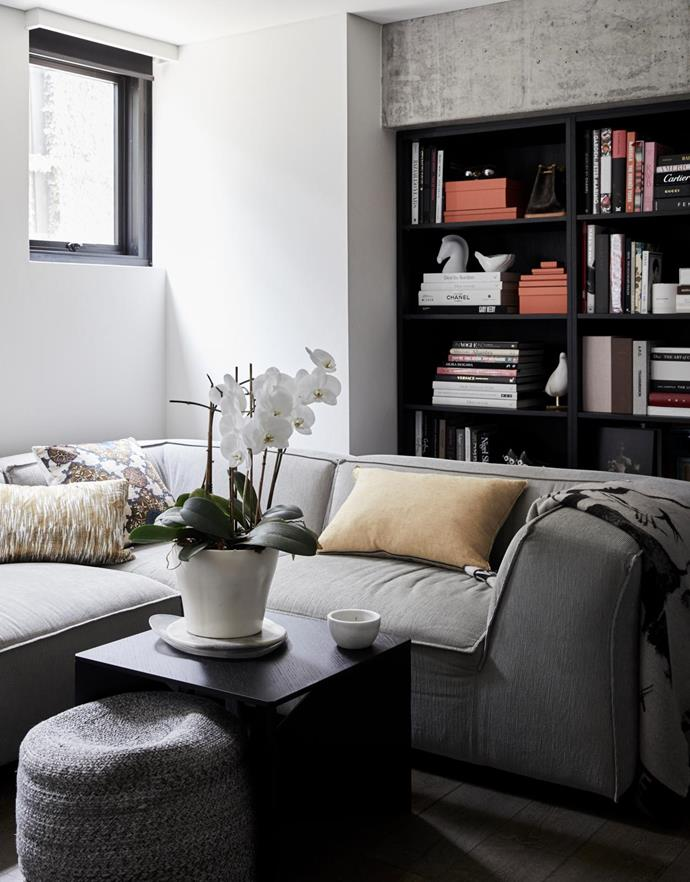 """""""We wanted separate living spaces for when the girls get older,"""" says Kellie. This downstairs entertainment room is equipped with a TV, while the upstairs living area is reserved for """"family and conversation"""". Gotham modular sofa, Spence & Lyda. Calvert coffee table by Ferdinand Kramer, Cult. Ottomans, Kmart."""